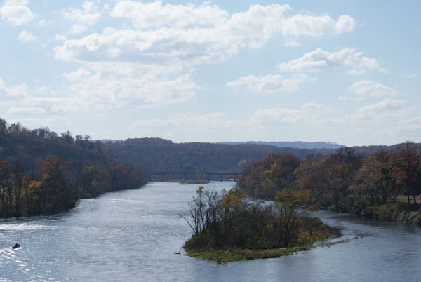 Landscape along both edges of the river featuring a bridge in the background.