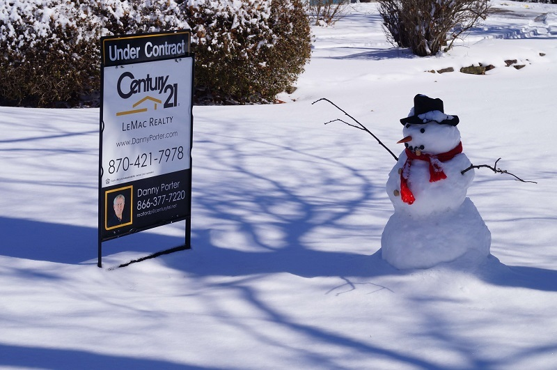 Snowman with hat and scarf, next to a Century21 Lemac Realty sign