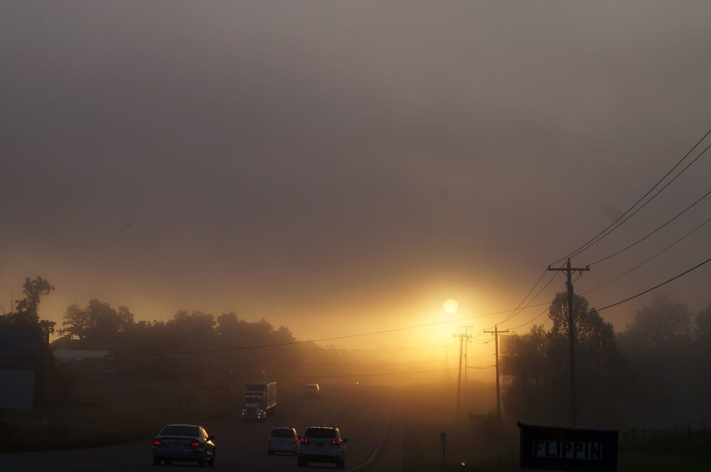 Highway leading into Flippin towards a foggy morning sunrise.